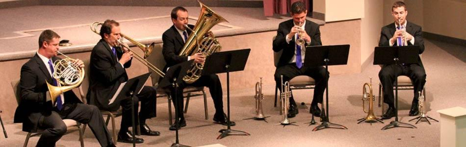Students play brass instruments at a concert